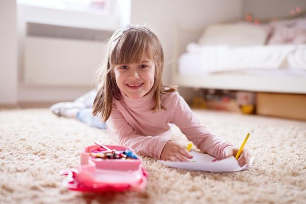 Hermosa y encantadora niña pequeña acostada en la alfombra de su habitación y dibujo con lápices de colores de madera sobre el papel.