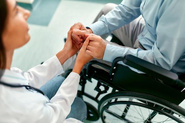 Hermosa enfermera caucásica en uniforme médico se ocupa de un paciente masculino maduro sentado en una silla de ruedas en el hospital, sosteniendo sus manos.