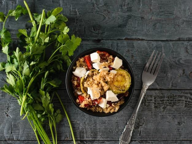 Hermosa ensalada de verduras al horno, quinoa y queso sobre una mesa negra