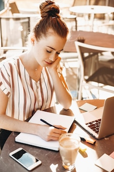 Hermosa escritora con cabello rojo y pecas haciendo su libro afuera en una cafetería.