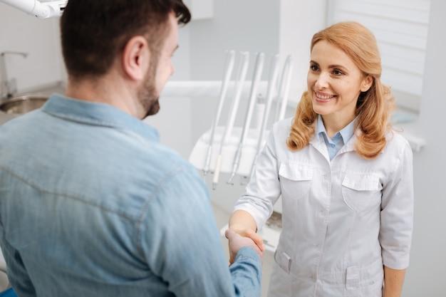 Hermosa especialista competente y agradable que parece encantada mientras estrecha la mano de su paciente y recibe palabras de agradecimiento de él.