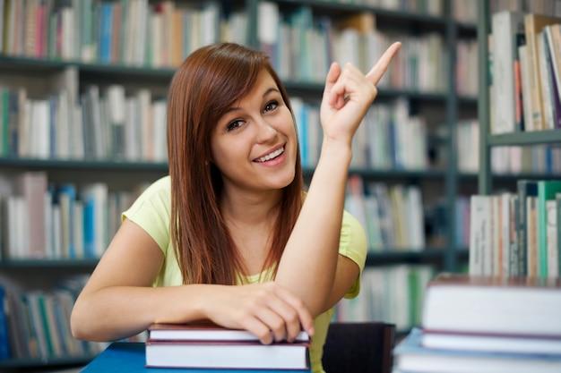 Hermosa estudiante apuntando a copyspace