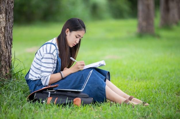 Hermosa estudiante asiática con libros y sonriendo y aprendiendo y educando en el parque en verano para relajarse
