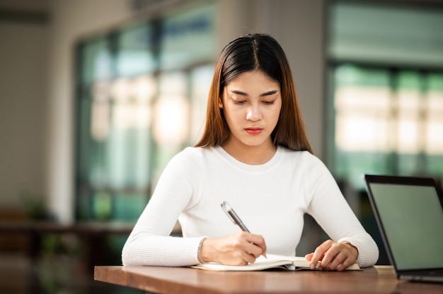 Hermosa estudiante asiática sentarse para el examen en el aula universitaria estudiantes sentados en la fila educación universitaria de estilo de vida