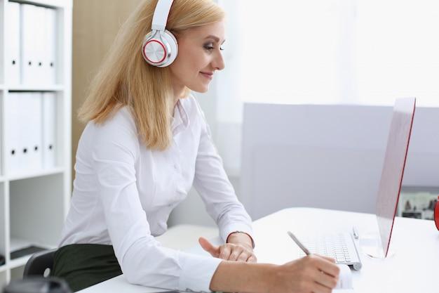 Hermosa estudiante con auriculares escuchando música y aprendiendo. sostenga el bolígrafo en la mano y mire el monitor de la computadora portátil