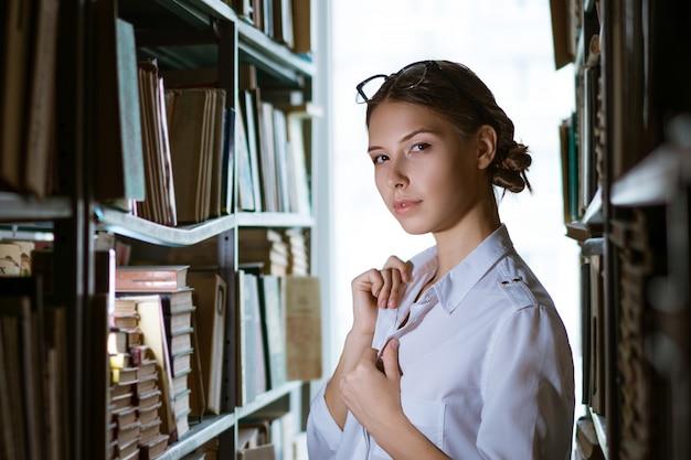 Hermosa estudiante con una camisa blanca se encuentra entre las filas de la biblioteca