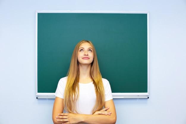 Hermosa estudiante feliz se encuentra cerca de la pizarra y mira cuidadosamente hacia arriba.
