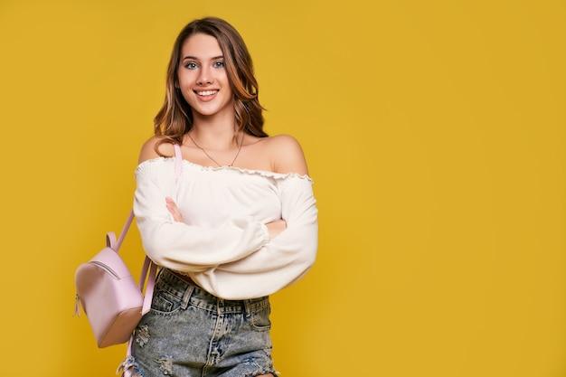 Hermosa estudiante con una mochila en una pared amarilla