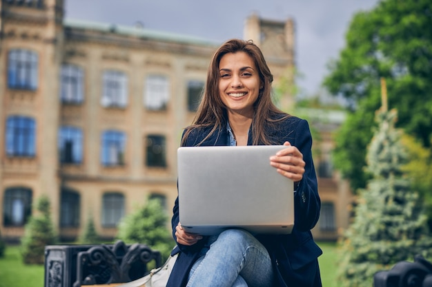 Hermosa estudiante en ropa casual trabajando fuera de la universidad en su computadora portátil y sonriendo