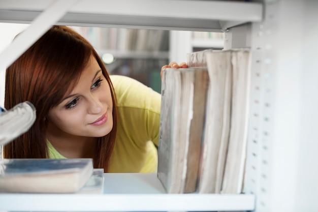 Hermosa estudiante seleccionando libro en biblioteca