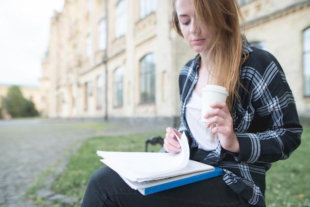 Hermosa estudiante sentada en un banco en el fondo de una universidad, leyendo un cuaderno y tomando café. concepto de estudiante aprendiendo en un descanso.