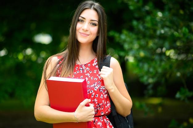 Hermosa estudiante sosteniendo un libro al aire libre