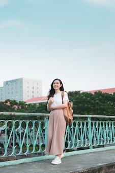 Hermosa estudiante universitaria asiática sosteniendo sus libros se encuentra y se viste con tela de moda callejera en el espacio público al aire libre con fondo de edificio moderno