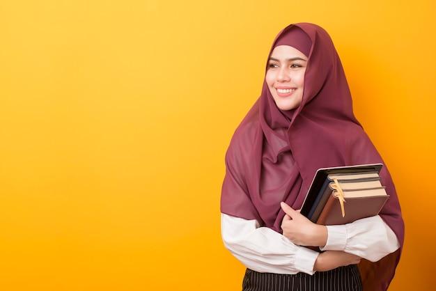 Hermosa estudiante universitaria con retrato hijab en amarillo