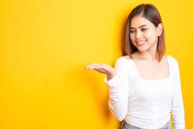 Hermosa estudiante universitaria está sonriendo en amarillo