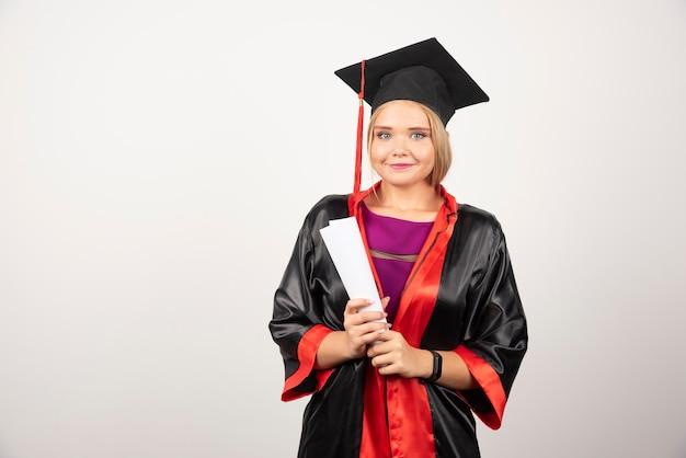 Hermosa estudiante en vestido con diploma.