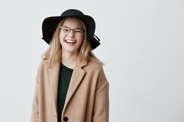 Hermosa eufórica adolescente con elegantes lentes, sombrero negro y abrigo, disfrutando de su vida, mirando y sonriendo, llena de alegría y felicidad. concepto de personas y estilo de vida