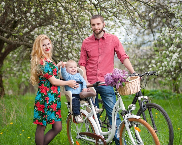 Hermosa familia en una bicicleta en el jardín de primavera