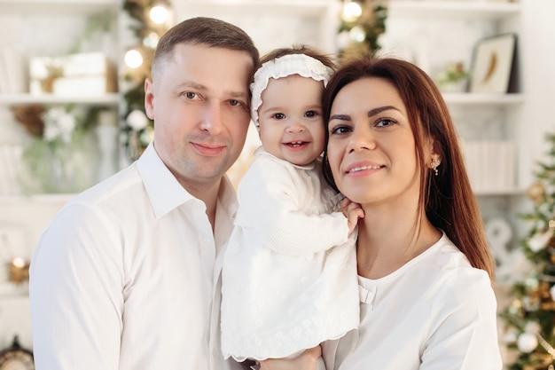 Hermosa familia caucásica alegre de madre, padre y niña linda en ropa blanca sonriendo a la cámara.