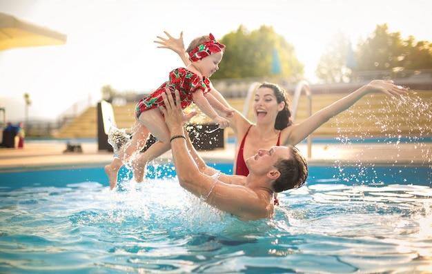 Hermosa familia divirtiéndose en una piscina