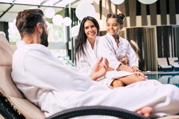 Hermosa familia feliz en batas de baño están felices juntos mientras están sentados en el salón de spa