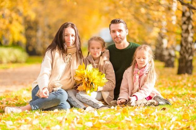 Hermosa familia feliz de cuatro en otoño día al aire libre