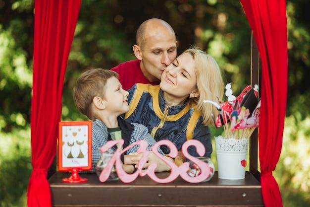 Hermosa familia feliz descansando y tomando fotos de vacaciones en el bosque, sesión de fotos en la cabina de besos