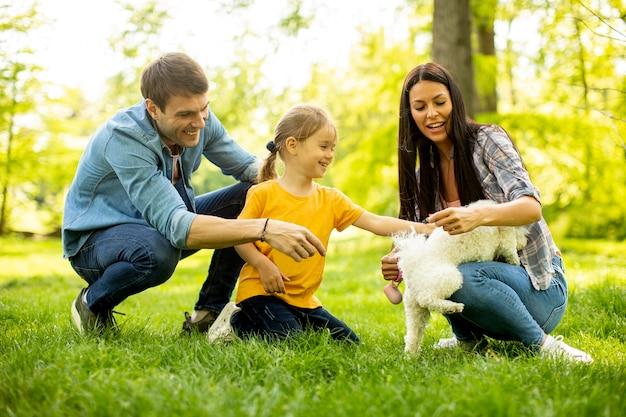 Hermosa familia feliz se divierte con el perro bichon al aire libre en el parque