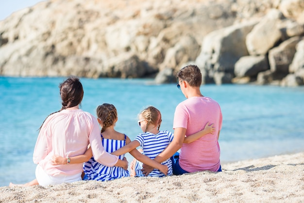 Hermosa familia feliz con niños caminando juntos en la playa tropical durante las vacaciones de verano