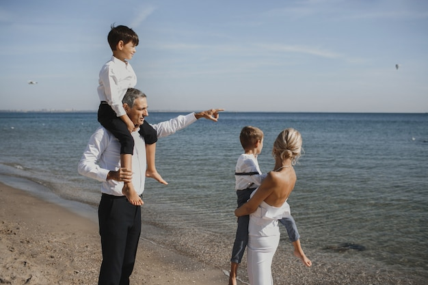 Hermosa familia está mirando el paisaje impresionante, padres y dos hijos, en el soleado día de verano