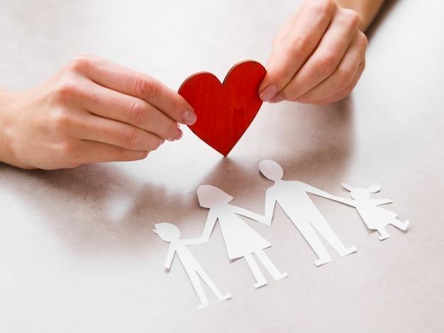 Hermosa familia de papel con un corazón de papel rojo