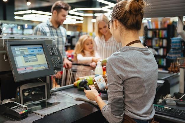 Hermosa familia de pie en el mostrador de efectivo