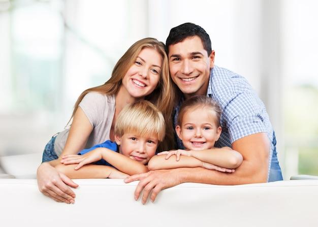 Hermosa familia sonriente en la habitación en el sofá