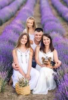 Hermosa familia y su perrito en un campo de lavanda. foto de verano en colores morados.