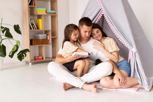 Hermosa familia de tiro largo pasar tiempo juntos en casa con espacio de copia