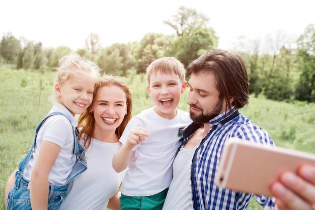 Hermosa familia está tomando selfie. guy sostiene el teléfono y mira hacia abajo. todos los demás están mirando por teléfono y sonriendo.