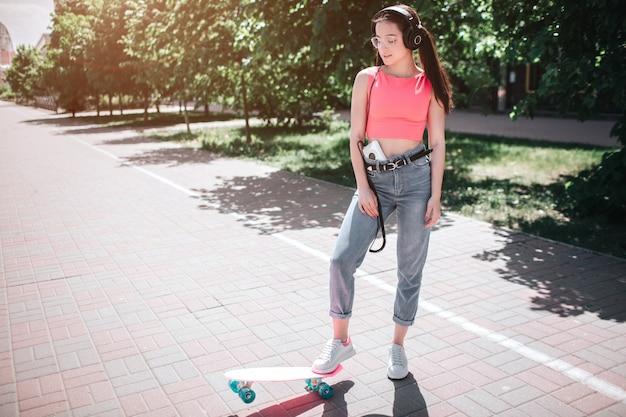 Hermosa y fantástica chica está de pie en la calle en un día soleado y posando. ella está sosteniendo un pie en el patín. hay un reproductor de música en sus pnats y montones en su cabeza.