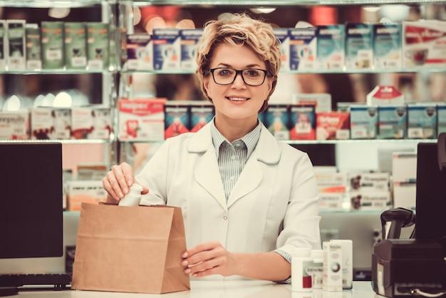 Hermosa farmacéutico está empacando medicina y sonriendo.