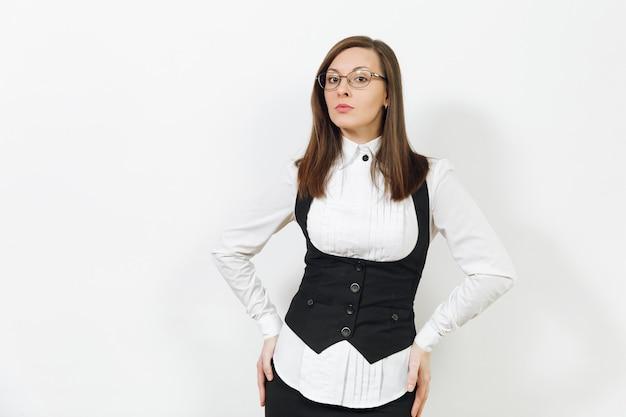 Hermosa feliz joven caucásica sonriente mujer de negocios de cabello castaño en traje negro, camisa blanca y gafas mirando a cámara aislada sobre fondo blanco. gerente o trabajador. copie el espacio para publicidad.
