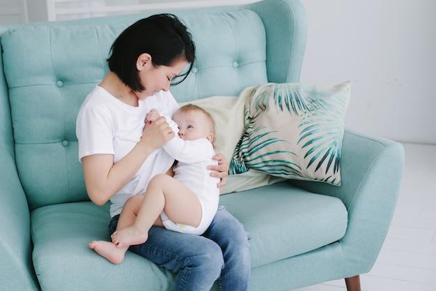 Hermosa feliz joven madre asiática abrazando a su pequeña hija en el dormitorio
