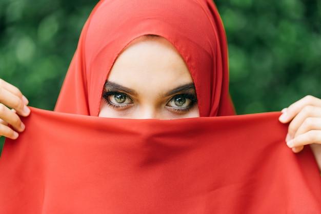 Hermosa de feliz mano de mujer musulmana joven levanta la tela de la cara con el hijab rojo