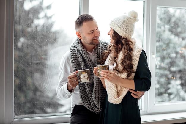 Hermosa y feliz pareja casada joven junto a la ventana