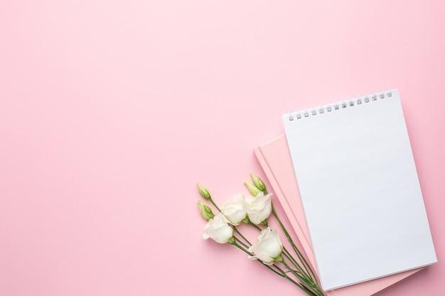 Hermosa flor blanca y cuaderno en rosa