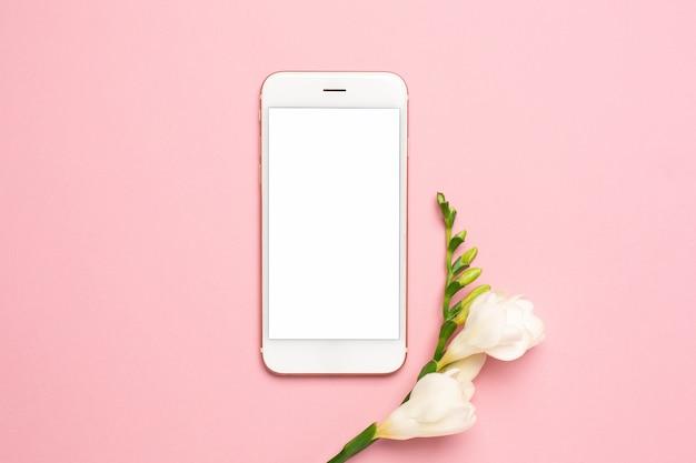 Hermosa flor blanca y teléfono móvil sobre fondo rosa