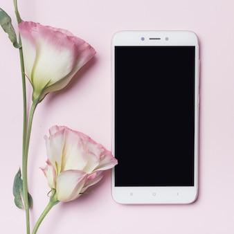 Hermosa flor de eustoma y teléfono inteligente contra el fondo rosa