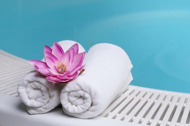 Hermosa flor de loto en toallas al borde de una piscina en el spa beauty club