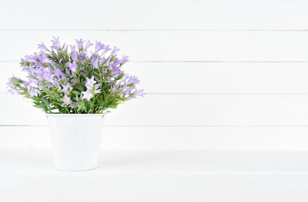 Hermosa flor morada en una olla sobre fondo blanco de madera