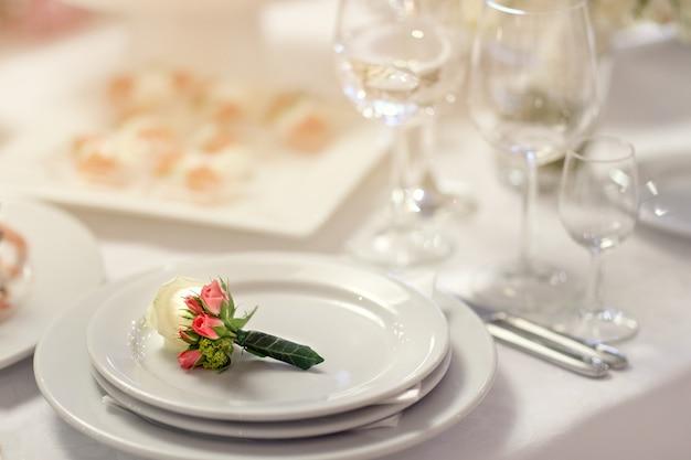 Hermosa flor en el ojal se encuentra en un plato blanco