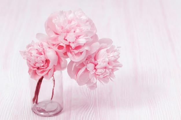 Hermosa flor de peonía en florero sobre fondo borroso
