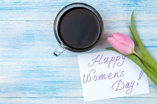 Hermosa flor rosa tulipán y café y texto feliz día de la mujer en la superficie de madera azul